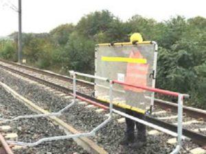 agent posant une barrière limitative sur voie ferroviaire